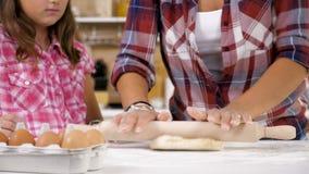 Abschluss herauf Gesamtlänge 4K der Mutter und des jungen Tochterbackens und zusammen kochen an der Küche stock footage