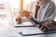 Abschluss herauf Geschäftsmann berechnen über Budget mit der Anwendung von calculato Lizenzfreie Stockfotos
