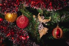 Abschluss herauf großes Gold und rotes Funkelnball- und Glasengelsweihnachten auf Baum lizenzfreie stockbilder