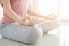 Abschluss herauf Hand- und Hälftekörper der gesunden Frau sitzen in Lotos Yogasitz Junge gesunde Frauensitzenlageübung im Haus stockfotografie