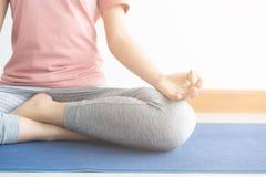 Abschluss herauf Hand- und H?lftek?rper der gesunden Frau sitzen in Lotos Yogasitz Junge gesunde Frauensitzenlage?bung im Haus stockfotos
