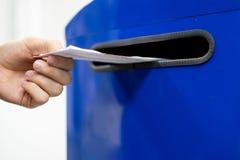 Abschluss herauf Handtropfenbuchstaben und Dokumente im blauen Postbox in Postpost f lizenzfreie stockfotos