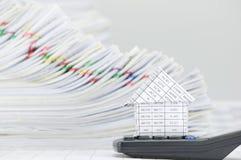 Abschluss herauf Haus auf Taschenrechner haben Überlastungsschreibarbeit als Hintergrund Stockfoto