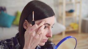 Abschluss herauf junge Frau bedeckt die Narben auf ihrem Gesicht mit Make-up stock footage