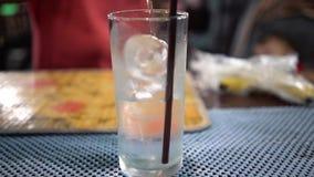 Abschluss herauf klares kaltes Wasser gießt in Glas mit Eiswürfeln Langsame Bewegung stock video