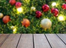Abschluss herauf leere dunkelbraune Holztischspitze mit unscharfem buntem Weihnachtsball und Lichter auf Weihnachtsbaumhintergrun lizenzfreie stockfotos