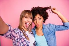 Abschluss herauf lustige Verschiedenartigkeit des Fotos zwei lässt sie ihre Damen, die spielerisch sind, selfies nehmen, Luftküss stockfoto