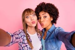 Abschluss herauf lustige Verschiedenartigkeit des Fotos zwei lässt sie ihre spielerischen Damen selfies nehmen, Luftkusskokette z lizenzfreie stockfotos