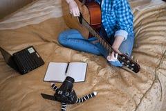 Abschluss- herauf Mädchen in der zufälligen Kleidung auf Bett spielt Akustikgitarre und schreibt Blog auf DSLR-Kamera Lizenzfreie Stockfotografie