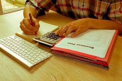 Abschluss herauf Mannhand unter Verwendung des Taschenrechners und Schreiben machen Anmerkung mit Ca Lizenzfreies Stockbild