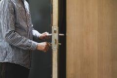 Abschluss herauf Personenhand im karierten Hemd öffnet Tür unter Verwendung der Schlüssel stockfotos