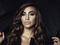 Abschluss herauf Porträt einer herrlichen Frau mit dem luxuriösen glänzenden gewellten Haar und perfekte bilden das Halten der br stockfoto