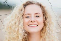Abschluss herauf Schuss der gelockten reizenden jungen Frau hat breites glänzendes Lächeln, betrachtet positiv Kamera, hat frohen stockfotografie