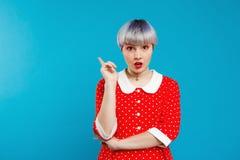Abschluss herauf umgekipptes schönes dollish Mädchen des Porträts mit dem kurzen hellvioletten Haar, das rotes Kleid über blauem  Stockfoto
