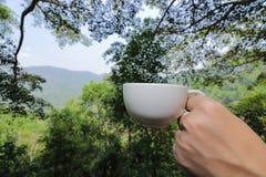 Abschluss herauf weiße Kaffeetasse wird durch Hände des Reisenden gegen schönen grünen Natur- und Gebirgshintergrund gehalten Lizenzfreies Stockfoto