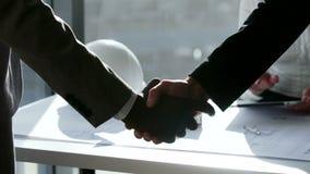 Abschluss herauf zwei Teilhaber rütteln Hände beim Treffen vor großem panoramischem Fenster in der Zeitlupe stock video