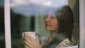 Abschluss oben Äußerer trinkender warmer Morgentee der durchdachten traurigen Brunettefrau und Träumen