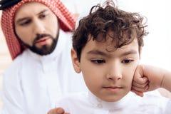 Abschluss oben Arabischer Mann bittet um Verzeihen vom kleinen beleidigten Sohn lizenzfreie stockfotografie