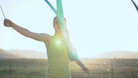 Abschluss oben Attraktives weibliches Turnertanzen mit blauem Band herein draußen bei Sonnenaufgang oder Sonnenuntergang Dünner T stock video footage