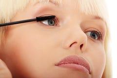 Abschluss oben auf dem schönen Handeln der jungen Frau bilden auf Wimpern. Stockfoto