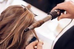 Abschluss oben Brown-Haarfrau tut Windenhaar im Schönheitssalon Friseur stellen Haar her, für Frau wellenartig zu bewegen lizenzfreie stockfotografie