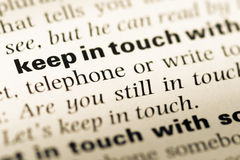 Abschluss oben der alten englischen Wörterbuchseite mit Wort bleiben mit in Kontakt stockbild