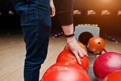 Abschluss oben der Bowlingspielspielerhand, die roten Ball vom Schüsselaufzug nimmt Stockfotografie