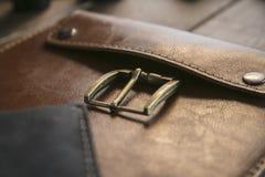 Abschluss oben der braunen ledernen handgemachten Handtasche mit Bronzeverschluß auf Holztisch Lizenzfreies Stockbild