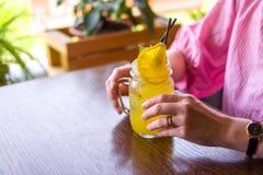 Abschluss oben der glücklichen Frau, die gelbes Cocktail mit orange Scheibe am Café - Getränke, Leute und Lebensstilkonzept trink Lizenzfreie Stockbilder