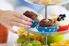 Abschluss oben der Hand, die kleinen Kuchen vom Kuchenstand nimmt Lizenzfreies Stockbild