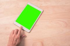 Abschluss oben der intelligenten Telefontablette der Handnote mit grünem Hintergrund auf Holz Stockfoto