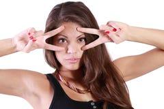 Abschluss oben der jungen Frau schaut durch zwei Zeichen Frieden Stockfoto
