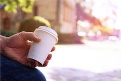 Abschluss oben der männlichen Handholding nehmen Kaffeetasse am Morgenti weg lizenzfreie stockfotografie