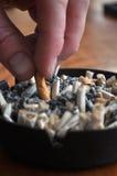 Abschluss oben der Zigarette, die heraus in Aschenbecher gerodet wird Lizenzfreie Stockbilder