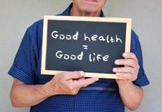 Abschluss oben des älteren Mannes, der eine Tafel mit der guten Gesundheit der Phrase hält, entspricht angenehmem Leben Lizenzfreie Stockbilder