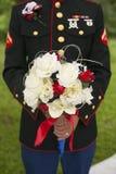 Abschluss oben des Armeesoldatbräutigams, der den Blumenstrauß der Braut hält Lizenzfreie Stockfotos