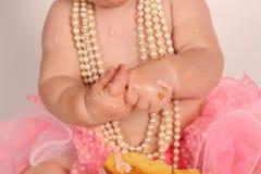 Abschluss oben des Babys, das den Kuchen ganz unordentlich isst Stockfoto