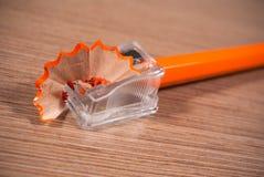 Abschluss oben des Bleistiftspitzers und des orange Bleistifts Lizenzfreies Stockbild
