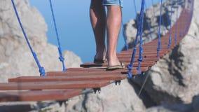 Abschluss oben des extremen Mannes der Füße geht auf das Seil auf langer hängender Brücke über dem Abgrund in der Zeitlupe 3840x2 stock video footage