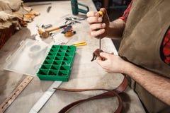 Abschluss oben des Handgerbers führt Arbeit über Tabelle mit Werkzeugen durch lizenzfreies stockbild