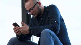 Abschluss oben des jungen traurigen Mannes sitzt nahe panoramischem Fenster und schlägt durch den Schirm an seinem Handy leicht stock video footage