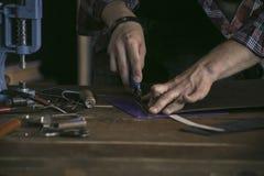 Abschluss oben des Mannhandlederherstellers führt Arbeit über Tabelle mit Werkzeugen durch Lizenzfreie Stockfotos
