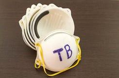 Abschluss oben des weißen Maskenstapels und des Wortes TB in der Maske auf schwarzem hölzernem Hintergrund Stockfoto
