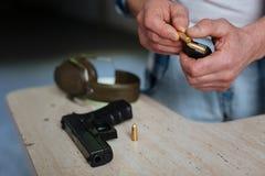 Abschluss oben einer Kugel, die in das Patronenclip gesetzt wird Stockfotos