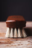 Abschluss oben einer Schuhglanzbürste auf einem rustikalen Hintergrund Lizenzfreie Stockfotografie