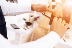 Abschluss oben Friseur ` s Hände kämmen heraus gerades blondes Haar der Frau am Schönheitssalon Lizenzfreies Stockfoto