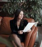 Abschluss oben Geschäftsfrau, die im Geschäftszentrum sitzt und Dokumente liest stockfotos