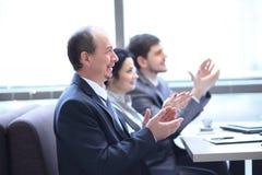 Abschluss oben Geschäftsteam, das den Sprecher, sitzend an dem Arbeitsplatz applaudiert stockfoto