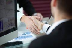 Abschluss oben Händedruck von Teilhabern über dem Schreibtisch lizenzfreie stockbilder