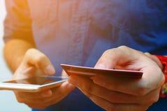 Abschluss oben intelligenten Telefons des Gebrauches des jungen Mannes und der halten Kreditkarte, s Stockfotografie